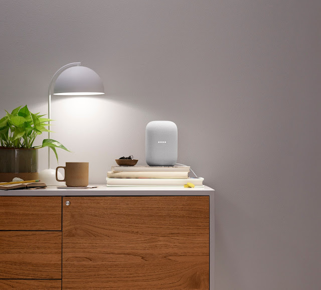 A Nest Audio device sits on a side table next to a lamp and a cup of coffee
