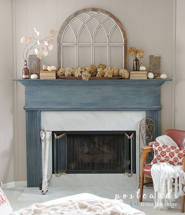 Love this cozy fall fireplace with the painted mantel and arched window. #manteldecor #fallmantel #fireplacedecor