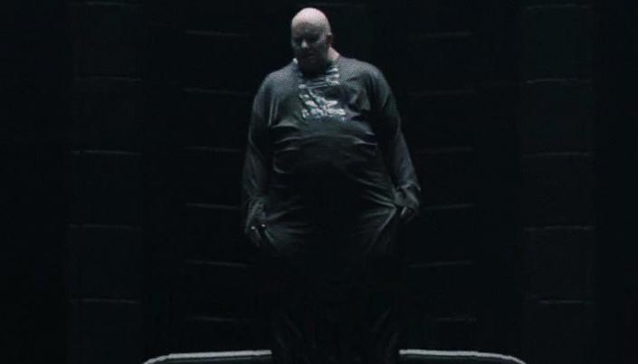 Imagem: o personagem Barão Harkonnen, um homem enorme, gordo, pálido e careca em roupas pretas, flutuando numa sala enorme e escura.