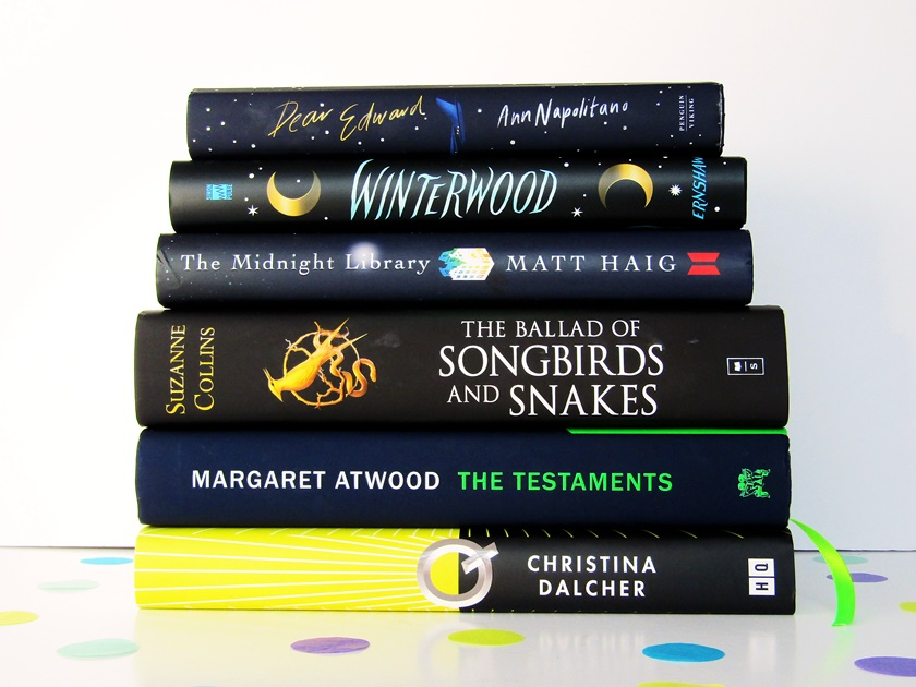 A photo of a stack of navy and black books stacked in width order against a white background. From top to bottom, the books shown are Dear Edward by Ann Napolitano, Winterwood by Shea Enshaw, The Midnight Library by Matt Haig, The Ballad of Songbirds and Snakes by Suzanne Collins, The Testaments by Margaret Atwood, and Q by Christina Dalcher.
