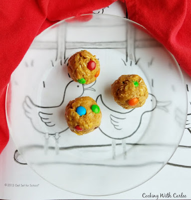 3 monster cookie dough balls on glass plate over coloring page