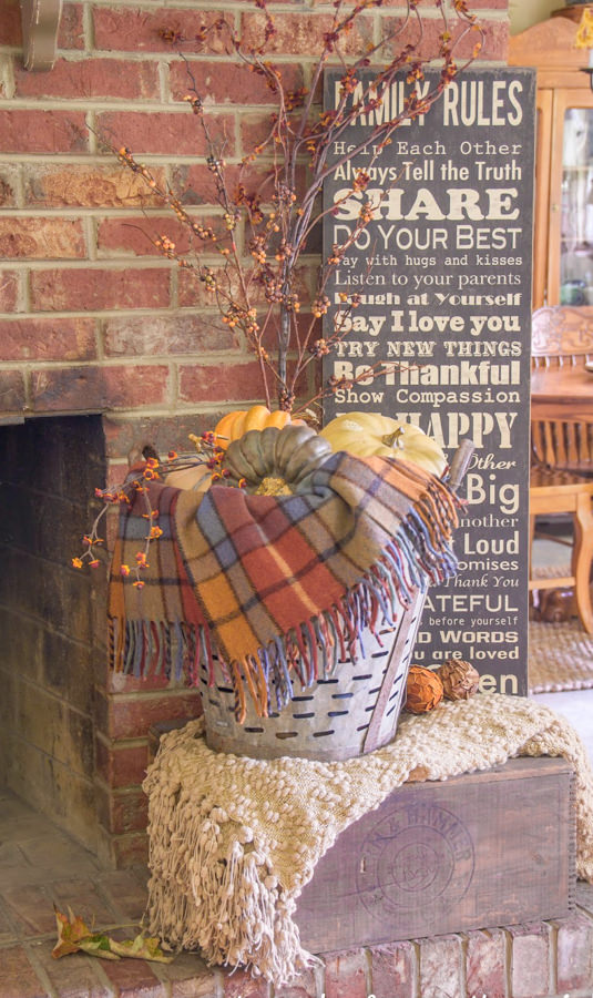 plaid blanket and fall flowers in a vintage olive basket