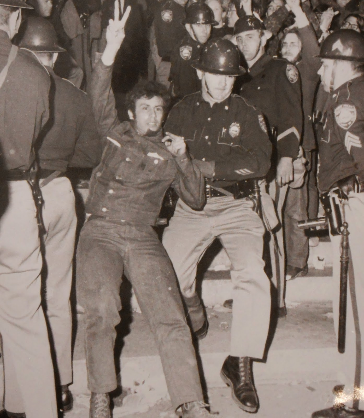 A black and white photograph of a young man being grabbed by a policeman as he throws up a peace sign.