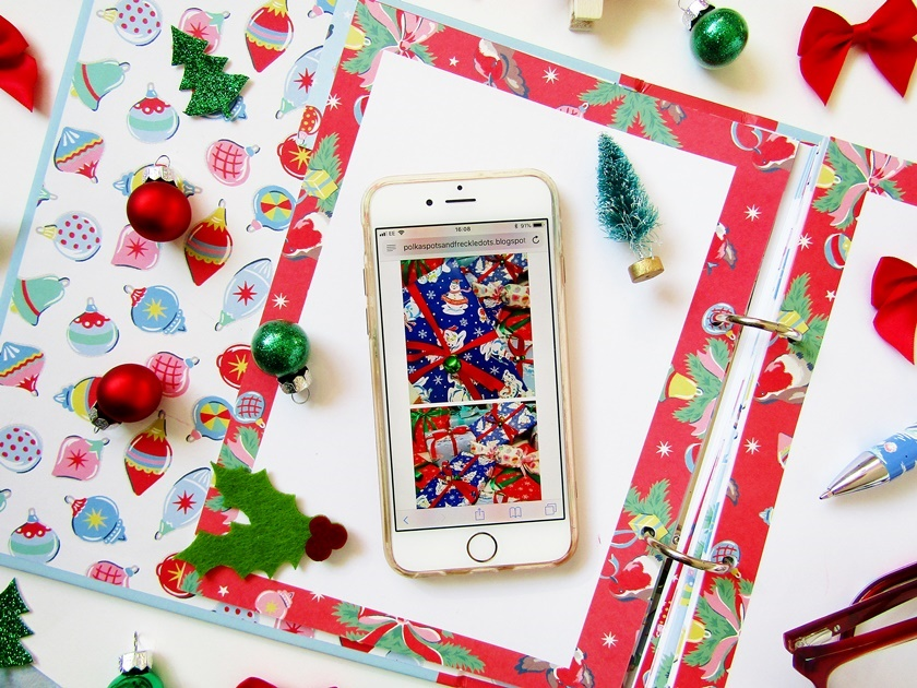 A Christmas flatlay image taken from above showing an open Christmas organiser topped with an  iPhone, and surrounded by small Christmas decorations like mini baubles, bows, and Christmas trees in red and green.