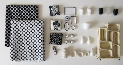 Selection of modern black and white dolls' house miniatures arranged on a desktop.