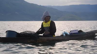 Fisherman paddling dugout canoe solu Samosir Island