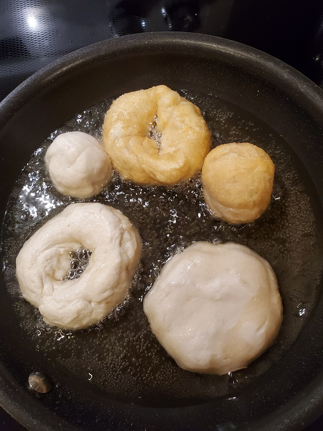 this is pizza dough frying in a fry pan in oil