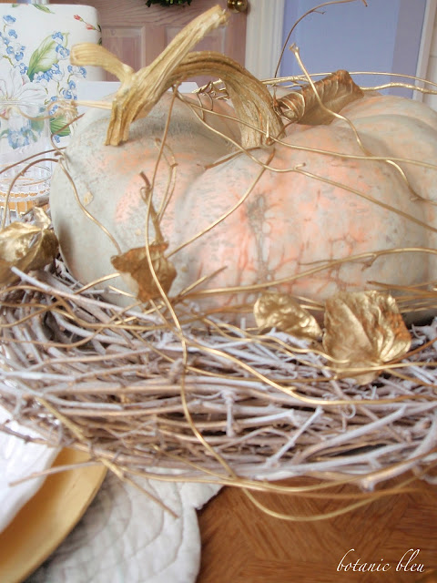 Thanksgiving gold and white table setting with cinderella pumpkin on a white and gold vine base