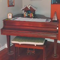 Baby grand piano in a corner with a crèche on it