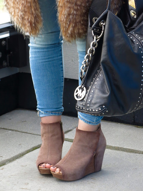 skinny jeans with a long, faux-fur vest, open-toe wedge booties, and MK bag