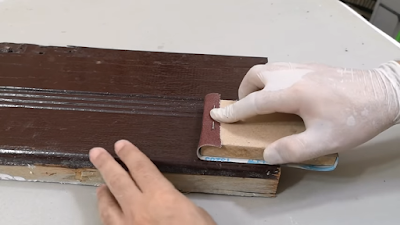 صنفرة الدهان من على سطح قطعة خشبية