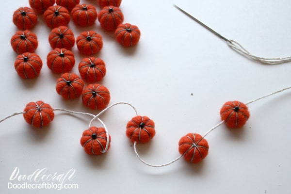 Just use a large darning needle and some twine and string them through, leaving about 2 inches of twine between each pom-pom.