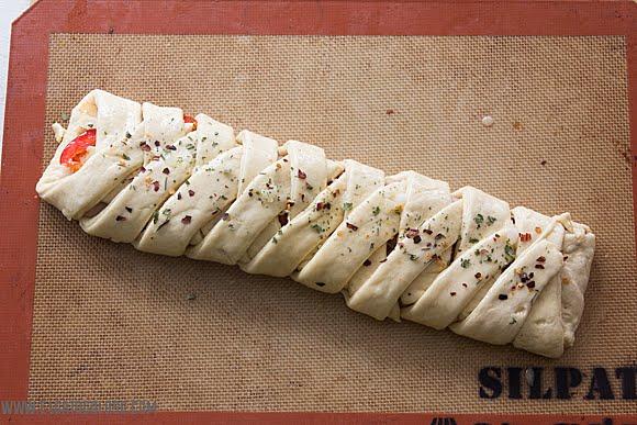 Stromboli trenzado con mortadela, queso y pimientos rojos. vía www.elgatogoloso.com