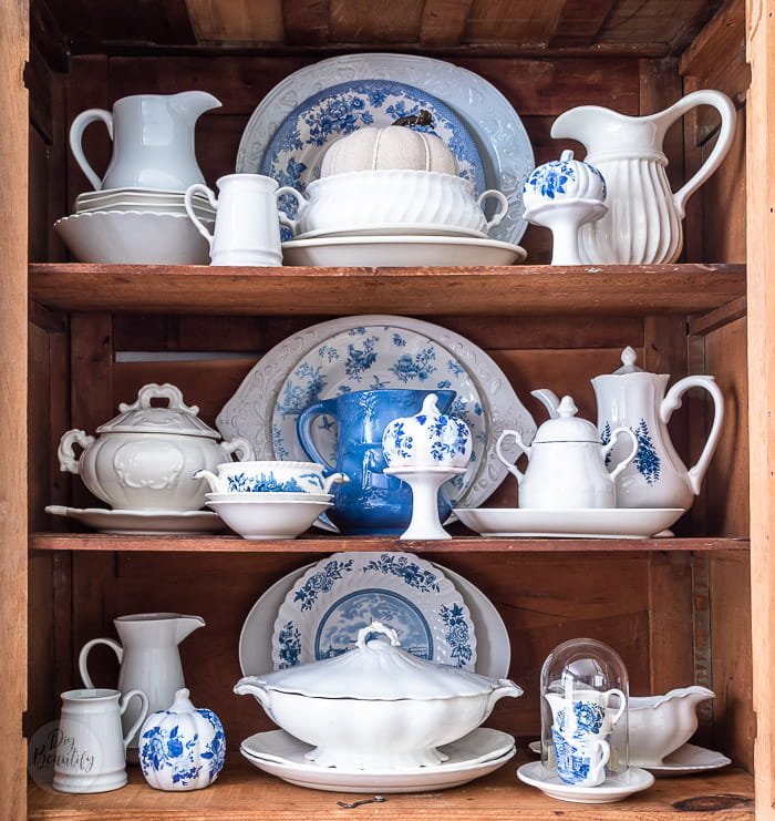 pine hutch filled with white ironstone, blue and white transferware and blue and white floral pumpkins