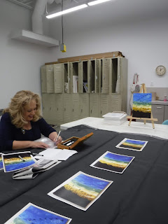 Sioux City artist Brenda Thelen holds a craft knife as she prepares a stencil for students to use in a painting class she will be teaching at the Sioux City Art Center. Paintings on a black tablecloth show each step of the project.