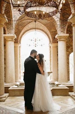 bride and groom kiss in atrium