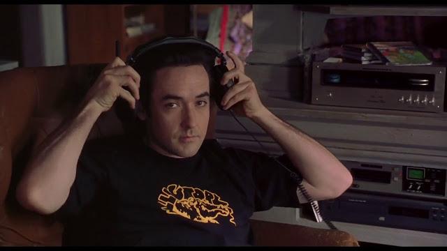 john cusack mirando a cámara en Alta fidelidad (2000)