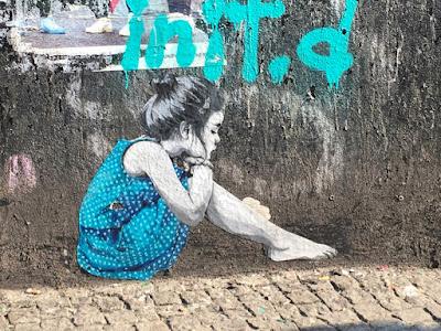 Mädchen in blauem Kleid auf grauer Fassade