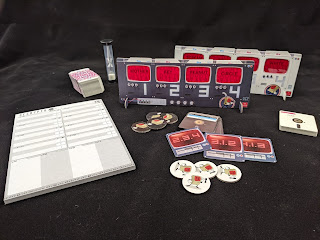 The components: two cardboard standees with red cellophane windows, one black and one white. A stack of cards with red markings on them to obscure the blue text; when these cards are slid into the display stands, the text becomes visible. There are also two stacks of cards that resemble 5 ¼ inch floppy disks, one in white and one in black. There are four black tokens, four white tokens, a sand timer, and a pad of scoresheets.