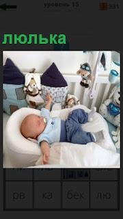 В люльке лежит младенец с соской во рту и спит в комнате среди игрушек
