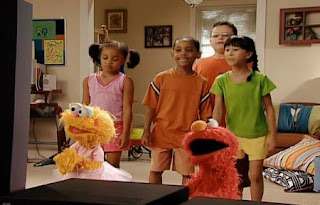 Zoe, Elmo and a few kids are watching Fuzzy and Blue And Healthy Too on TV. Sesame Street Happy Healthy Monsters