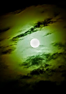 Full moon shining through a greenish cloud