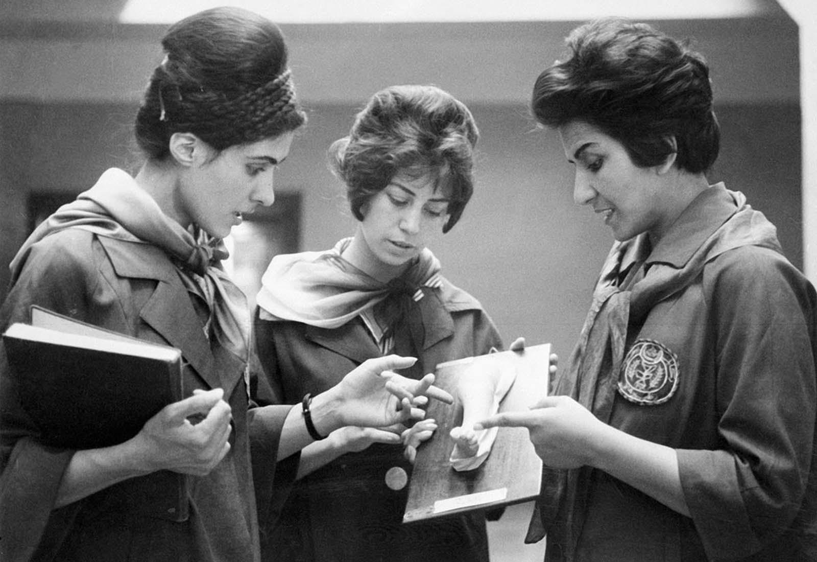 Fotografía tomada en 1962 en la Facultad de Medicina en Kabul de dos estudiantes de medicina afganos que escuchan a su profesor (a la derecha) mientras examinan un yeso que muestra una parte de un cuerpo humano.