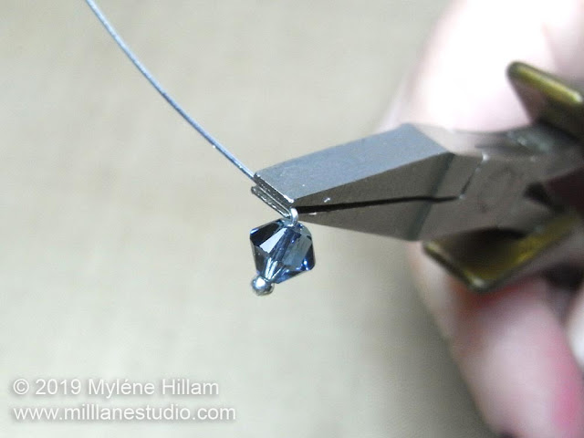 Bending the head pin above the bead at a right angle.