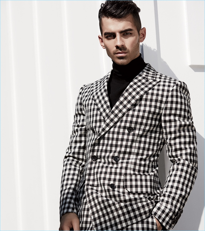 Joe Jonas sports a black and white check suit with a turtleneck by Bally