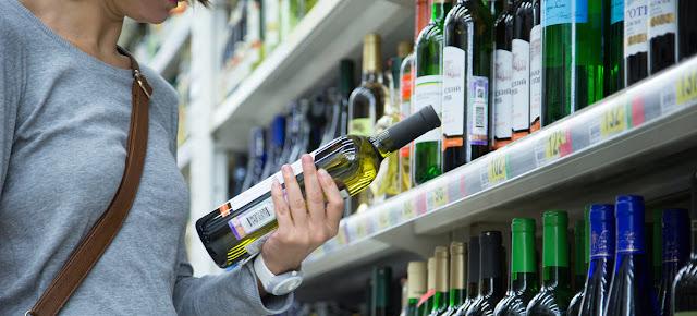 Una mujer observa una botella de vino en un supermercado de Moscú.OMS/Sergey Volkov
