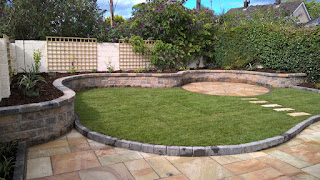Image of Curving Sandstone terrace raised lawn and beds