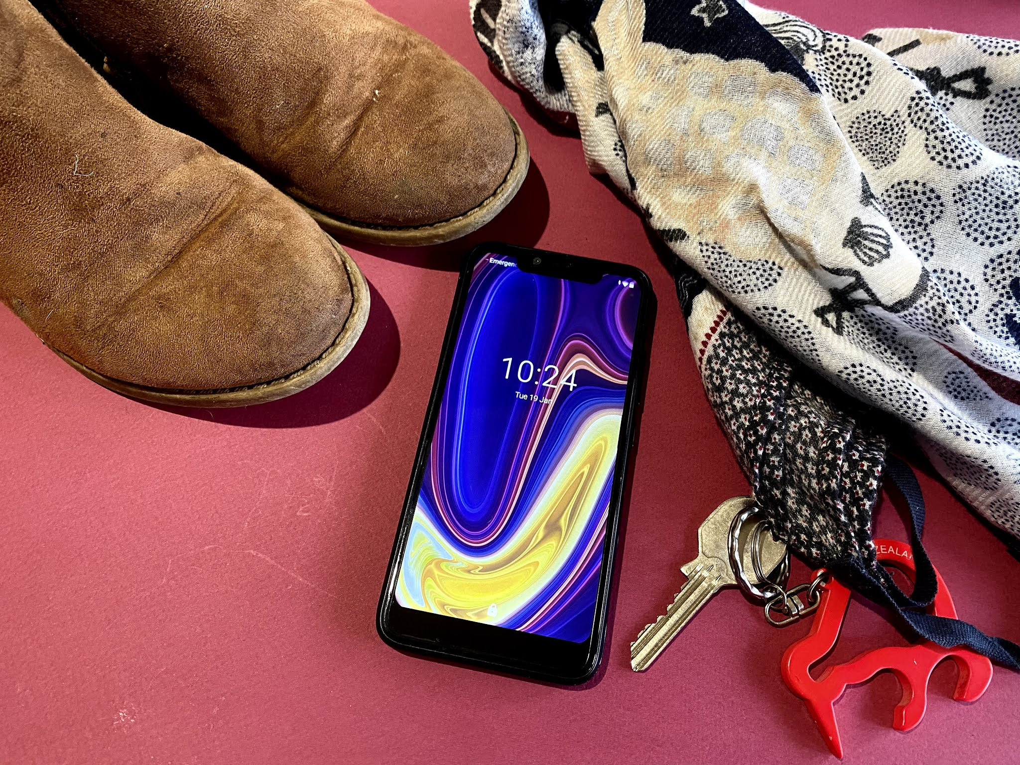 A cheap smartphone mobile next to a scarf, tween boots and keys