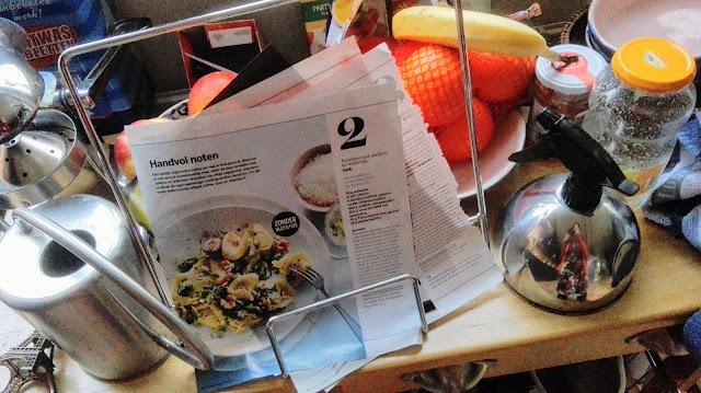 Tafeltje in keuken met receptenstandaard, fruit, lege flessen en een gieter.