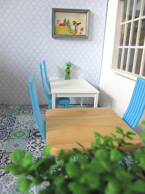 Modern dolls house miniature cafe scene, with blue and white tiled floor, white and grey wallpaper, white and beech tables, blue chairs and plants in the foreground.