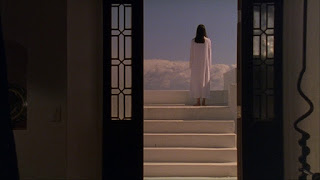 Looking out through a door to the rear view of a woman in white at the top of a flight of steps looking out over clouds