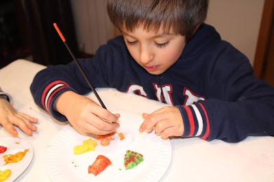 criança a pintar formas de Natal