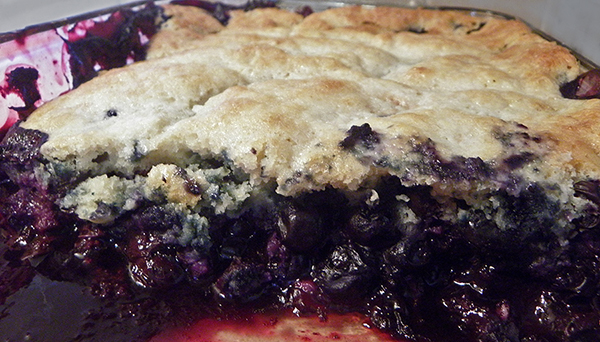 Pan of blueberry cobbler with some already eaten
