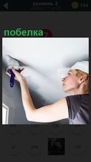 женщина занимается побелкой потолка кисточкой