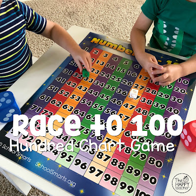 Kids playing math game with dice and hundreds chart.