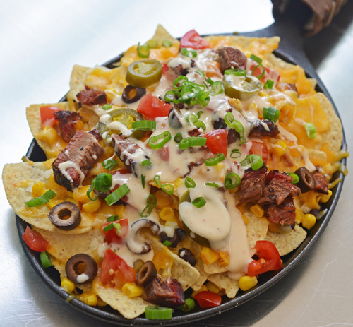 Green chile brisket nachos cooked on a Big Green Egg kamado grill.