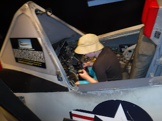 A boy wearing a brown hat sits in an airplane at the South Dakota Air Museum