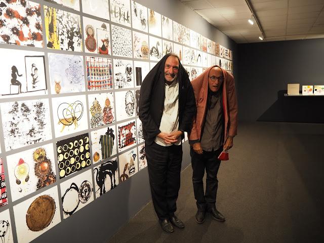 """Frederic Amat i Vicenç Altaió posen junts en una divertida imatge davant algunes de les obres que recull l'exposició """"Espai Llibres""""."""