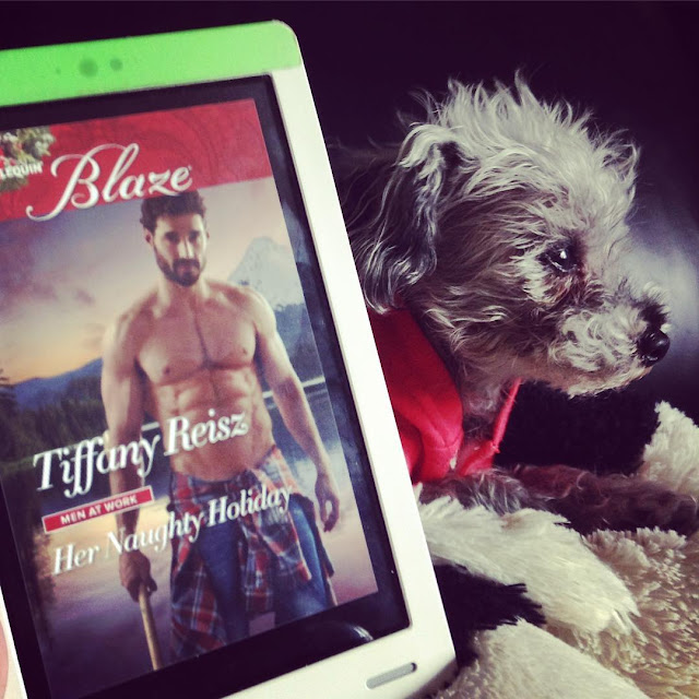 Murchie gazes into the distance from behind a white Kobo with the cover of Her Naughty Holiday on it. The cover features a dark-haired, bearded white man standing by a lake, sans shirt.