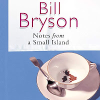 Notes from a Small Island audiobook cover.A teacup and spoon sit on a blue backdrop. The tealeaves in the almost-empty cup form the shape of the United Kingdom and Ireland.
