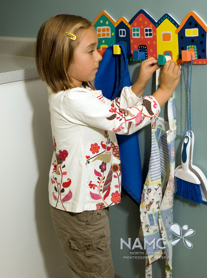 namc montessori functionality environment. child hanging apron