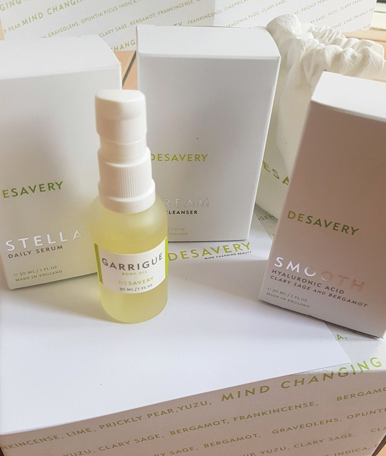 a selection of Desavery Skincare products including Stellar Daily Serum, Garrigue Body Oil, Dream Oil Cleanser, and Smooth Hyaluronic Acid all on a white box