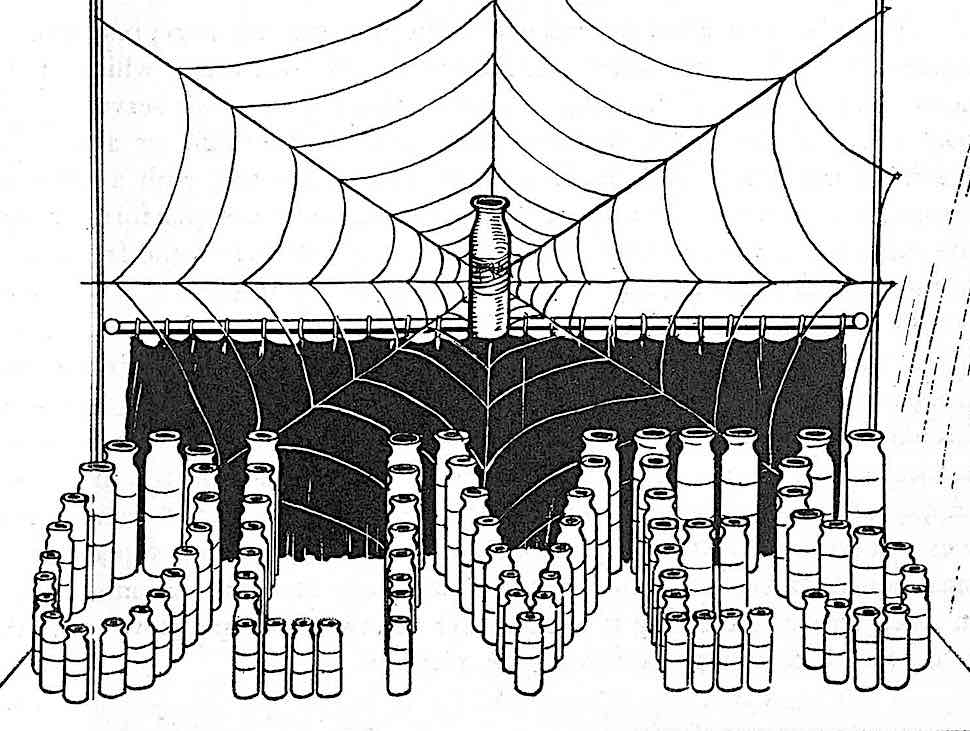 a 1923 store window display for bottled olive oil with a giant spider web