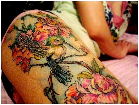 chica acostada con el tatuaje en la pierna de un colibri