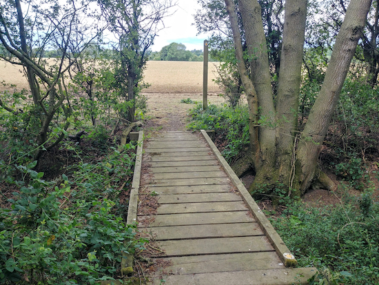 The footbridge leading to the open field, mentioned in point 13 above Image by Hertfordshire Walker released via Creative Commons BY-NC-SA 4.0