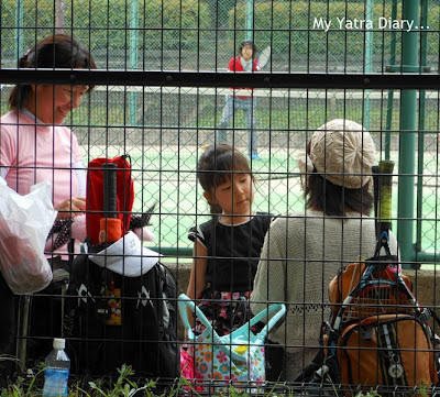 A child takes a break from tennis at Hibiya Garden - Tokyo, Japan